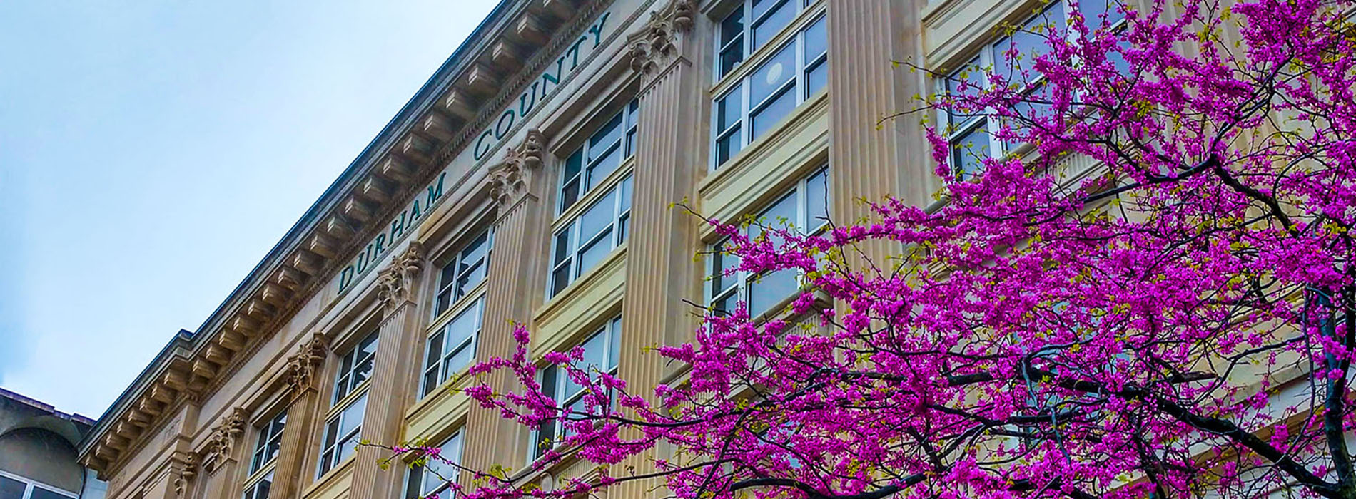 Front of Durham County Adminstration Building I with flowers in bloom
