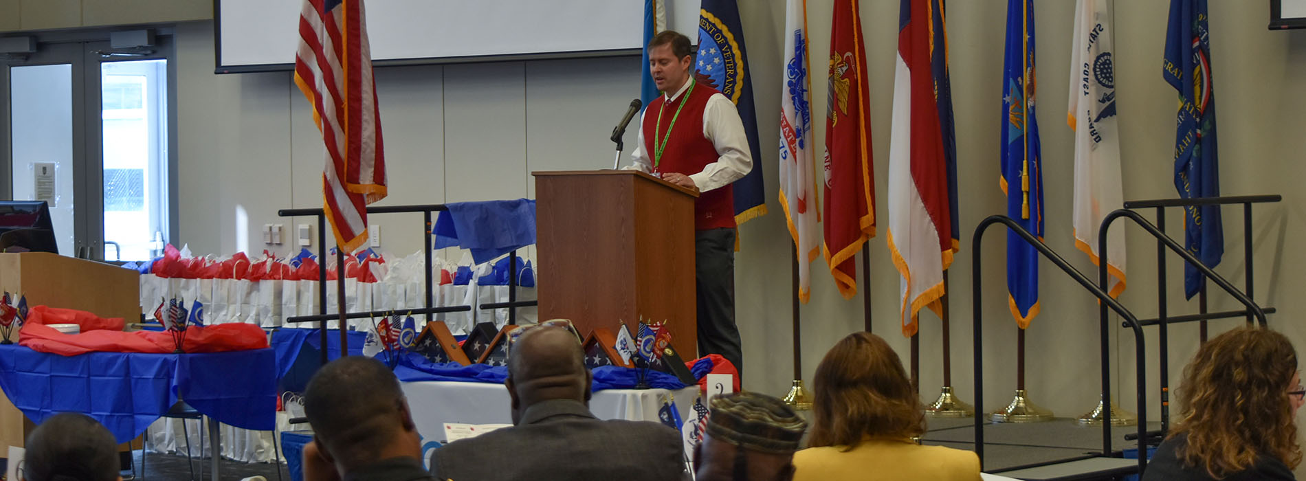 Speaker at podium at Veterans Day celebration in 2018 with audience